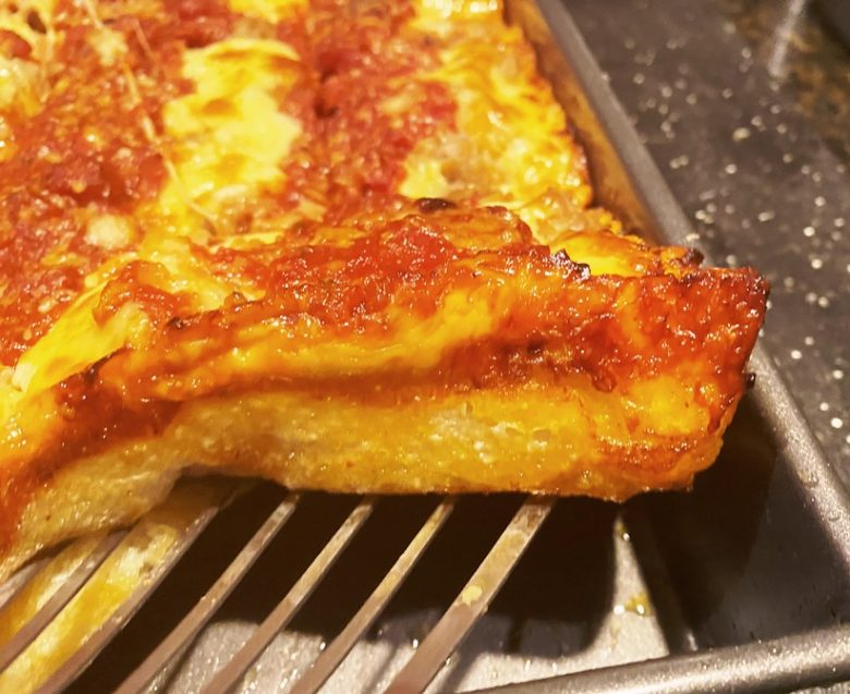 Detroit-style pizza with sausage and cheese, corner shot